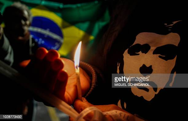 Supporters of Brazilian rightwing presidential candidate Jair Bolsonaro light candles in the front of the Albert Einstein Hospital in Sao Paulo where...
