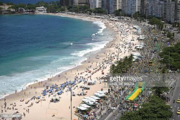 Supporters of Brazil's presidential rightfar candidate Jair Bolsonaro take part in a rally in Copacabana Rio de Janeiro on October 21 2018 Barring...