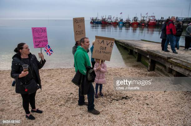 Supporters of Brexit stand on the shore as fishermen take part in a nationwide protest against the Brexit transition deal on April 8 2018 in...