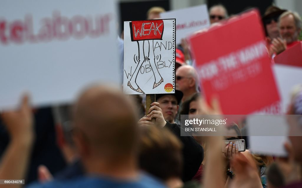 Supporters of Britain's main opposition Labour party hold a banner reading 'Weak and Wobbly', referring to Britain's Prime Minister Theresa May, as the party's leader Jeremy Corbyn speaks during a general election campaign rally in Reading, west of London, on May 31, 2017, as campaigning continues in the build up to the general election on June 8. PHOTO / Ben STANSALL