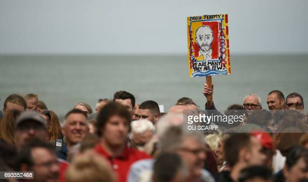 TOPSHOT Supporters of Britain's main opposition Labour Party hold placards as they wait for the leader Jeremy Corbyn to arrive at a campaign visit in...