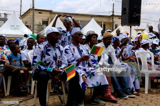 Supporters of Cameroonian President Paul Biya wear clothing emblazoned with his image as they celebrate his re-election in Yaoundé on November 6,...
