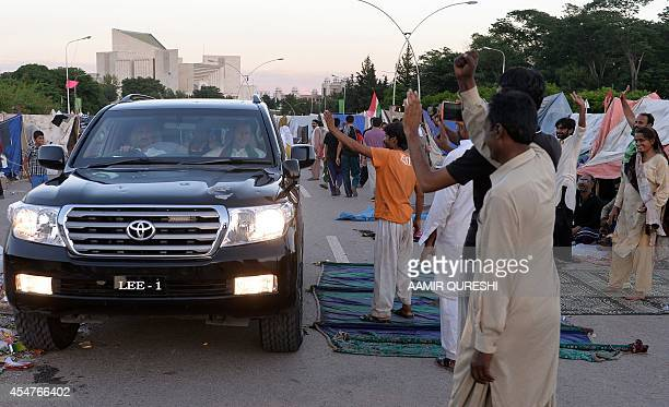 Supporters of Canadian cleric Tahir ul Qadri wave to Pakistani cricketerturned politician Imran Khan as he sits inside a vehicle as he arrives at an...