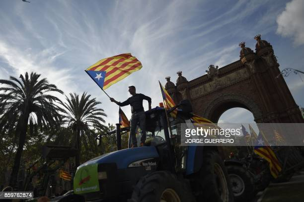 Supporters of Catalan independence wave Catalan flags as they drive with tractors through the Arc de Triomf in Barcelona on October 10 2017 Spain's...