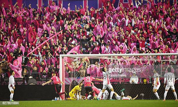 Supporters of Cerezo Osaka celebrate after the team scored the opener during the second half of the J-League promotion playoff final against Fagiano...