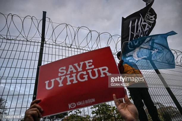 """Supporters of China's Muslim Uighur minority holds a placard reading """"Save Uighur"""" as a boy waves the flag of East Turkestan and an Islamic black..."""