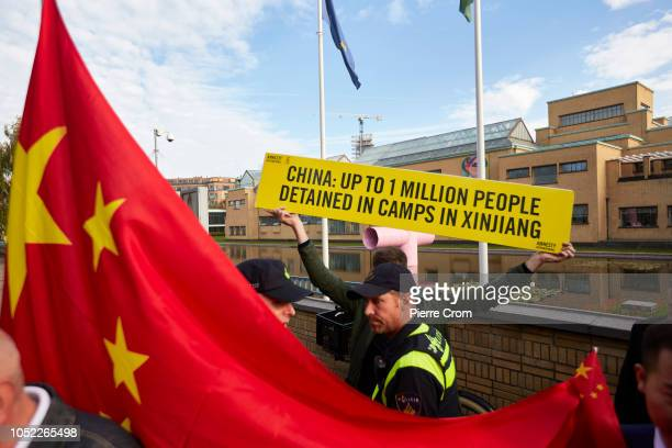 Supporters of Chinese Prime Minister Li Keqiang attempt to block an activist of Amnesty International holding a protest board reading China Up to 1...