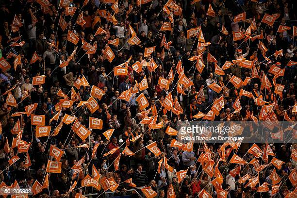 Supporters of Ciudadanos party wave flags during a campaign rally with Albert Rivera at Palacio de Vistalegre on December 13 2015 in Madrid Spain...