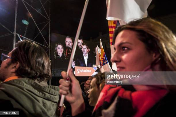 Supporters of Ciudadanos wave flags and watch a broadcast of their party leaders as they celebrate electoral victory in Barcelona Spain on Thursday...