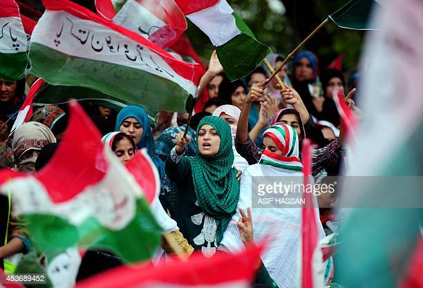 Supporters of cleric TahirulQadri wave flags at an antigovernment rally in Islamabad on August 16 2014 A populist cleric TahirulQadri led thousands...