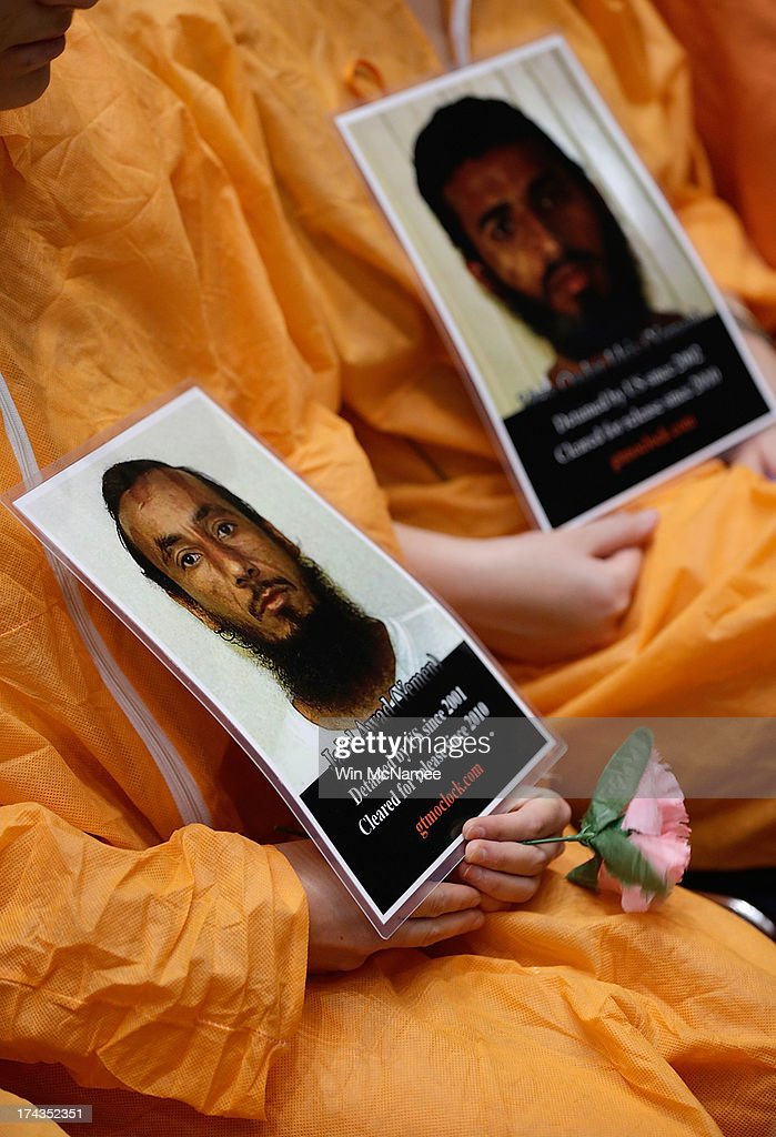 Supporters of closing the Guantanamo Bay Naval Base detention facility wearing orange prison style jumpsuits hold pictures of prisoners being held at the facility while sitting in the audience during a hearing of the Senate Judiciary Committee July 24, 2013 in Washington, DC. The committee heard testimony from a panel of witnesses on 'Closing Guantanamo: The National Security, Fiscal, and Human Rights Implications.'