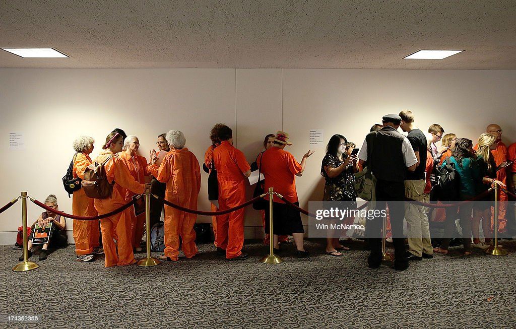 Supporters of closing the Guantanamo Bay Naval Base detention facility wearing orange prison style jumpsuits wait to be admitted to a hearing of the Senate Judiciary Committee July 24, 2013 in Washington, DC. The committee heard testimony from a panel of witnesses on 'Closing Guantanamo: The National Security, Fiscal, and Human Rights Implications.'