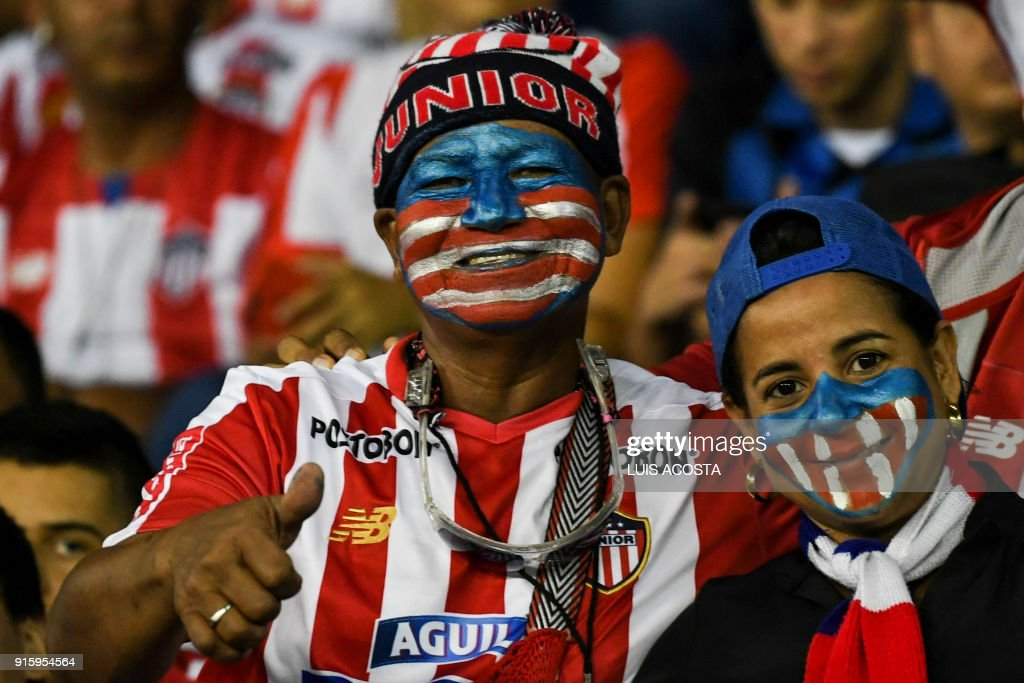 Supporters of Colombia's Junior cheer for their team before a Copa Libertadores football match against Paraguay's Olimpia at Roberto Melendez stadium in Barranquilla, Colombia, on February 8, 2018. / AFP PHOTO / Luis ACOSTA