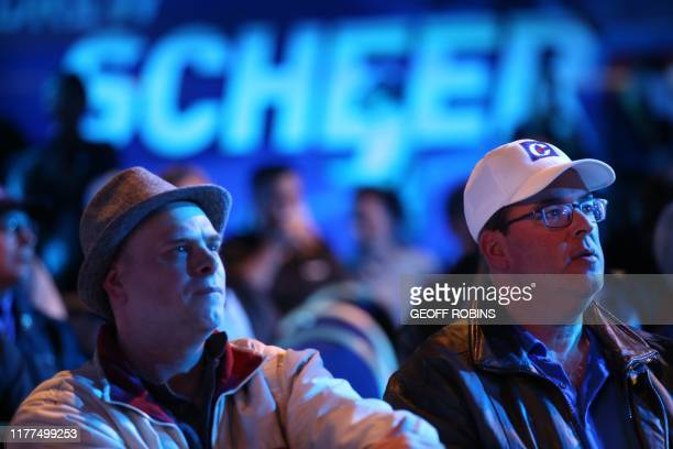 Supporters of Conservative leader Andrew Scheer react to the latest results during an election night rally in Regina Saskatchewan on October 21 2019