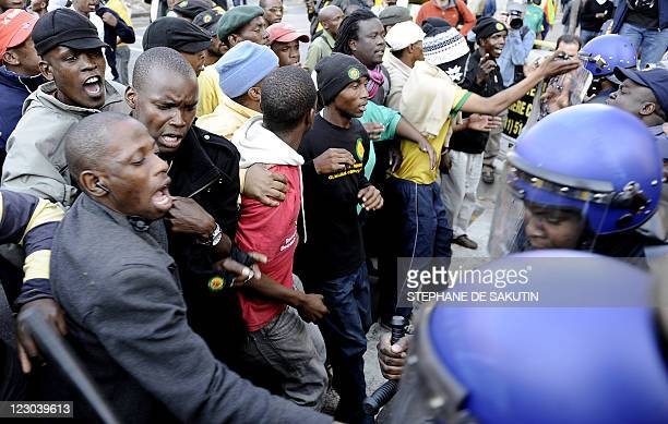 Supporters of controversial African National Congress youth leader Julius Malema face Police on August 30 2011 in Johannesburg ahead of his...