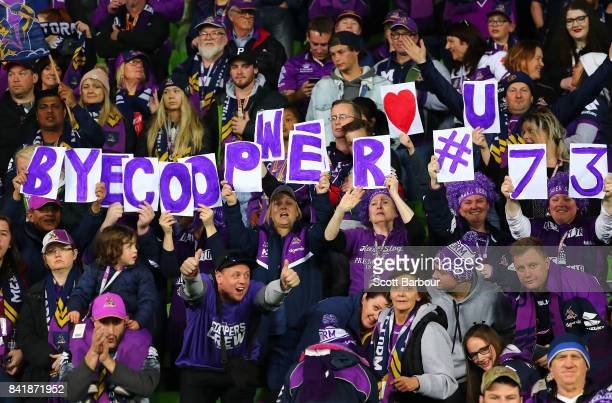 Supporters of Cooper Cronk of the Storm in the crowd hold signs aloft during the round 26 NRL match between the Melbourne Storm and the Canberra...