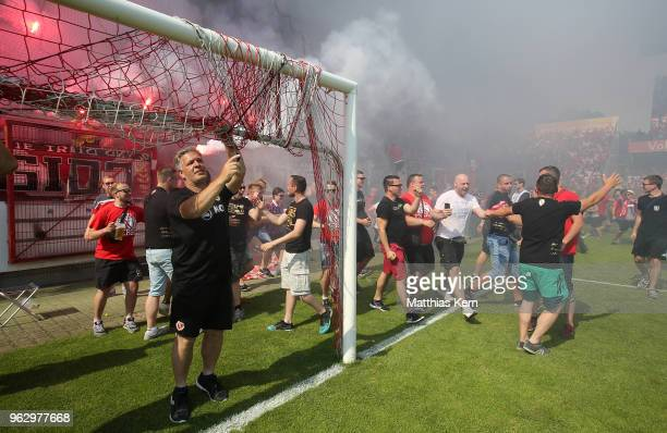 Supporters of Cottbus celebrate after their team moving up into the third league after the Third League Playoff Leg 2 match between FC Energie...