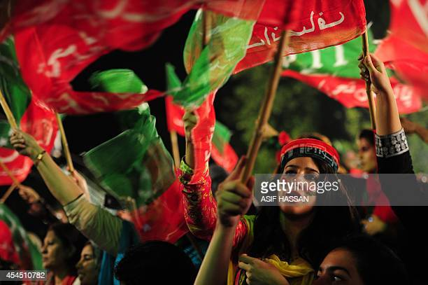 Supporters of cricketerturned politician Imran Khan wave party flags during an antigovernment protest near the prime minister's residence in...