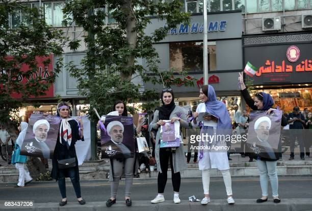 Supporters of current President of Iran Hassan Rouhani hold banners of Rouhani ahead of the Iranian presidential election in the streets of Tehran...