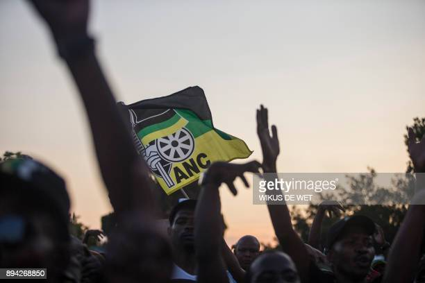 Supporters of Cyril Ramaphosa South African Vice President and presidential hopeful of the African National Congress hold an ANC flag outside NASREC...