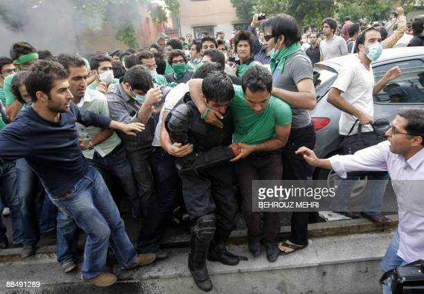 Supporters of defeated Iranian presidential candidate Mir Hossein Mousavi helps evacuate a injured riot police officer after he was beaten by...