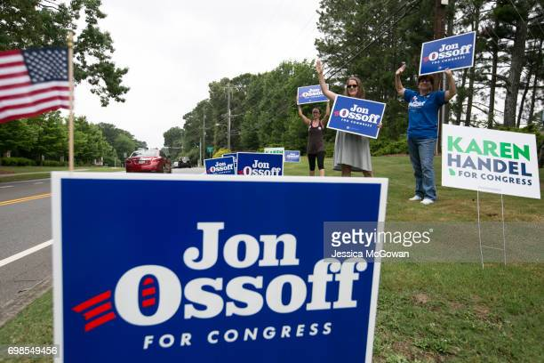 Supporters of Democratic candidate Jon Ossoff including Renee Taylor Krista Tomiko and Melissa Rickert of Marietta wave at cars passing by St Mary's...