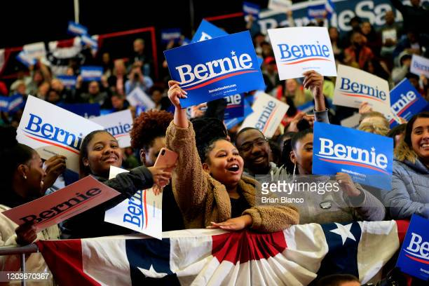 Supporters of Democratic presidential candidate Sen Bernie Sanders listen as he speaks during a rally and march to early vote on February 27 2020 at...