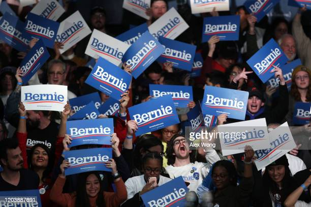Supporters of Democratic presidential candidate Sen Bernie Sanders cheer during his caucus night watch party on February 03 2020 in Des Moines Iowa...