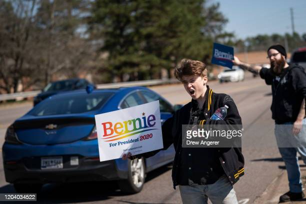 Supporters of Democratic presidential candidate Sen Bernie Sanders cheer and hold signs on the side of the road before the arrival of Sanders at a...