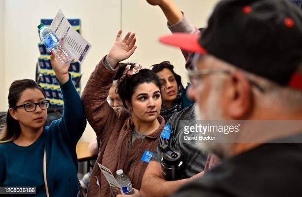 Supporters of Democratic presidential candidate Sen Bernie Sanders raise their ballots to be counted during a Nevada Democratic caucus at Coronado...