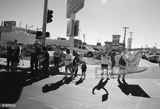 Supporters of Democratic presidential candidate US Senator John Kerry hold signs as his motorcade drives by October 23 2004 in Pueblo Colorado