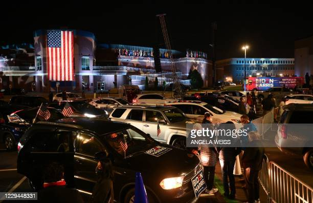 Supporters of Democratic presidential nominee and former Vice President Joe Biden check their phones for partial election results outside the Chase...
