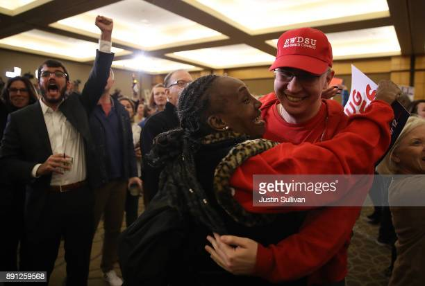 Supporters of democratic US Senator candidate Doug Jones celebrate as Jones is declared the winner during his election night gathering the Sheraton...