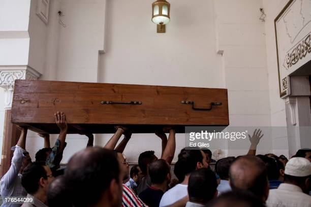 Supporters of deposed Egyptian President Mohammed Morsi carry a coffin inside the front door of the al Amin Mosque, prior to the funeral of...