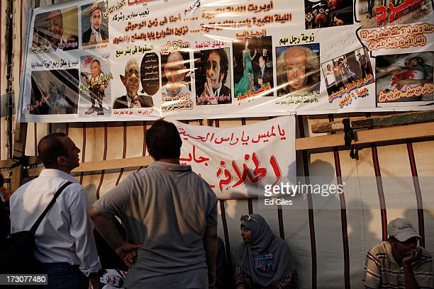 Supporters of deposed Egyptian President Mohammed Morsi look at a banner ridiculing Egyptian opposition figures including Mohammed ElBaradei at the...