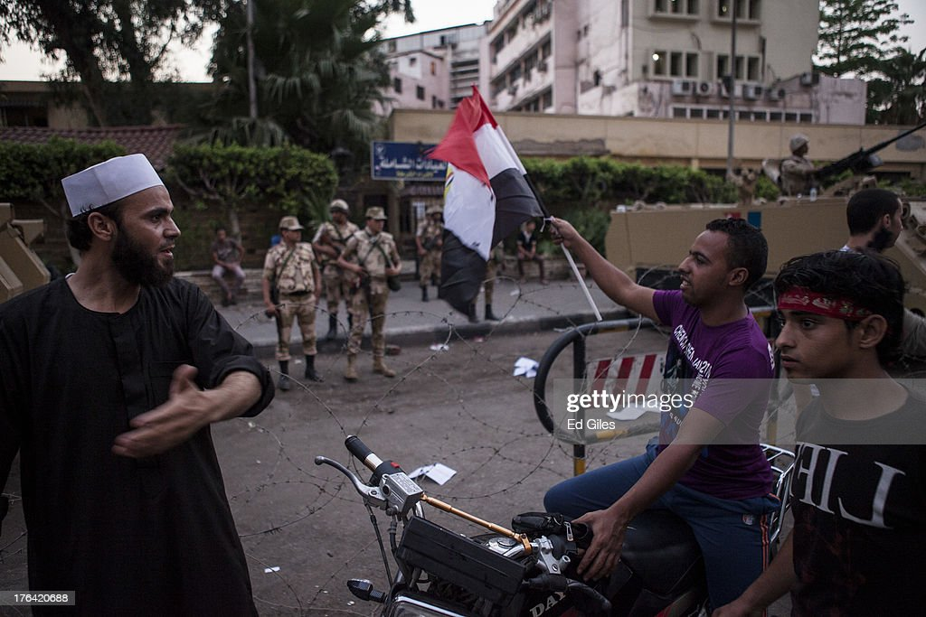 Supporters of deposed Egyptian President Mohammed Morsi walk past a group of Egyptian Soldiers during a protest march in the Giza district on August 12, 2013 in Cairo, Egypt. Egyptian security forces threatened to begin a siege of pro-Morsi protest camps in Cairo overnight on August 11, however Egypt's Interior Ministry appeared to have put off plans to crack down on protesters early on August 12. On Monday Egypt's judiciary also extended deposed President Morsi's detention for a further 15 days pending investigation into charges of his collaboration with the Palestinian Hamas movement. Morsi supporters have continued to protest at sites across Cairo over one month after the Egyptian military deposed Egypt's first democratically elected President, Mohammed Morsi, on July 3. (Photo by Ed Giles/Getty Images).