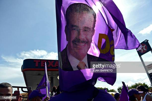 Supporters of Dominican presidential candidate for the Democratic Liberation Party Danilo Medina hold a flag with his portrait during a rally in...