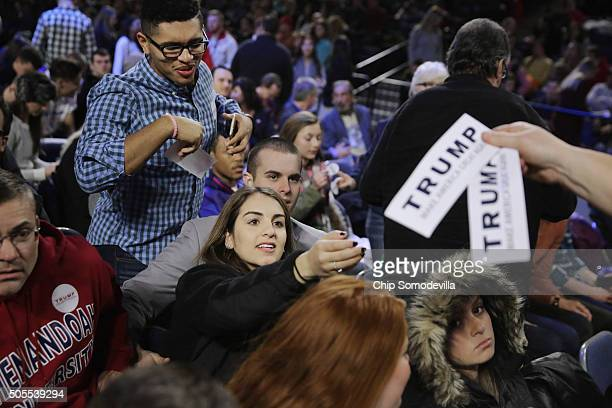 Supporters of Donald Trump reach for bumper stickers before the Republican presidential candidate delivers the convocation at the Vines Center on the...