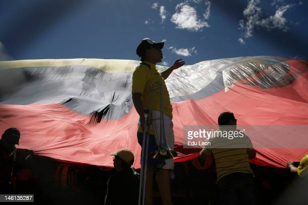 Supporters of Ecuador covered by an Ecuadorian flag before the match between Ecuador v Colombia at Atahualpa stadium during the sixth round of the...