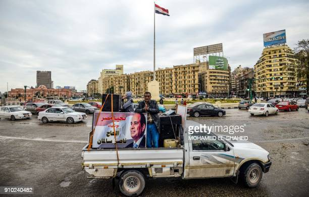 TOPSHOT Supporters of Egyptian President Abdel Fattah alSisi drive a pickup truck bearing his portrait and loudspeakers in the capital Cairo's Tahrir...