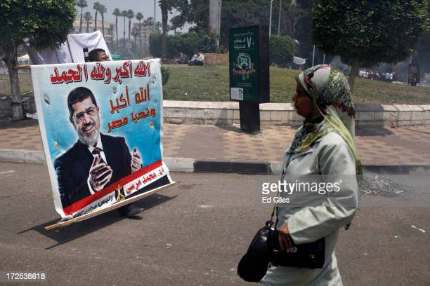 Supporters of Egyptian President Mohammed Morsi clean up debris after violent clashes at Cairo University the previous night on July 3 2013 in Cairo...