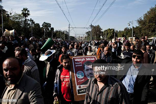 Supporters of Egyptian President Mohammed Morsi leave en masse from Egypt's Presidential Palace, after violent clashes the previous night, on...