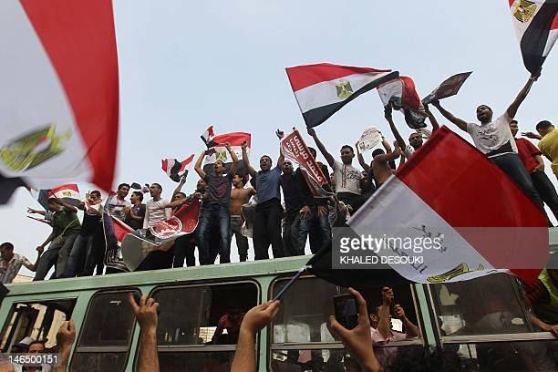 Supporters of Egypt's Muslim Brotherhood candidate Mohammed Mursi wave national flags during celebrations in Cairo's Tahrir square after the...