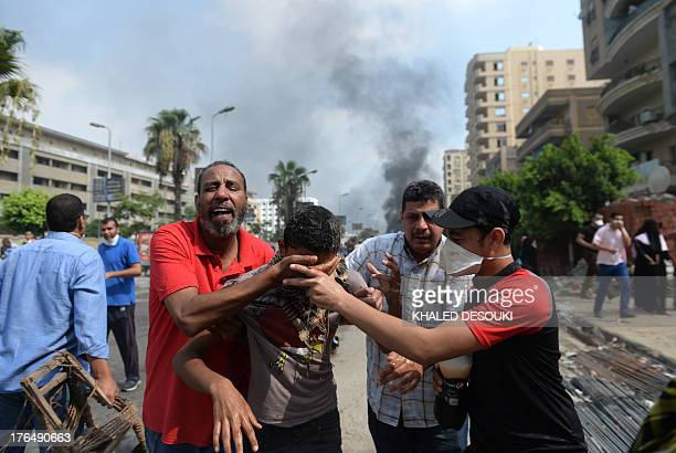 Supporters of Egypt's ousted president Mohamed Morsi and members of the Muslim Brotherhood run from tear gas smoke shot by police to disperse a...