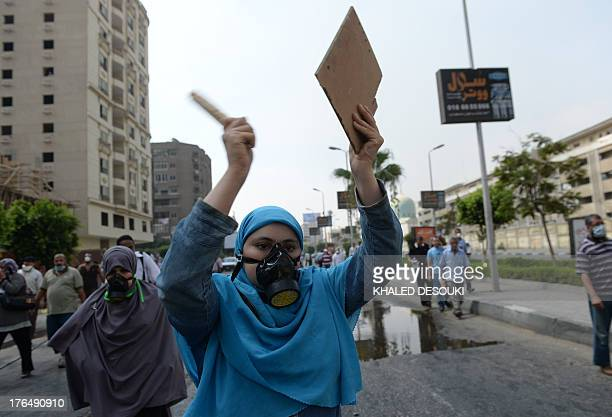 Supporters of Egypt's ousted president Mohamed Morsi and members of the Muslim Brotherhood protect their faces from tear gas smoke shot by police to...