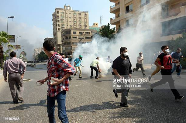 Supporters of Egypt's ousted president Mohamed Morsi and members of the Muslim Brotherhood run for cover from a tear gas canister fired by riot...