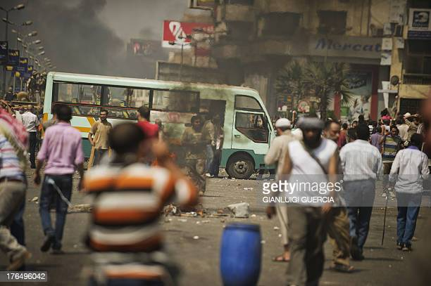 Supporters of Egypt's ousted president Mohamed Morsi clash with riot police on a street leading to Rabaa al-Adawiya square in Cairo on August 14 as...