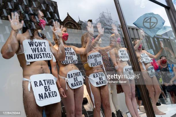 Supporters of environmental and Climate Change group Extinction Rebellion , protest against the ethics of the fashion industry by glueing their hands...