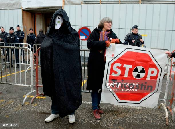 Supporters of Environmental group Greenpeace activists one dressed in black with nuclear logo on his mask demonstrate to support Greenpeace members...
