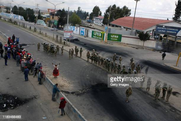 Supporters of Evo Morales Ayma shout slogans in front of the main entrance of Yacimientos Petroliferos Fiscales Bolivianos oil refinery as military...